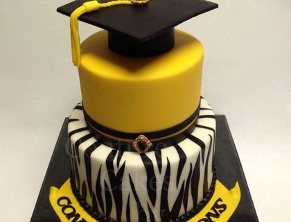 A graduation cake I made for a young lady who graduated from high school back in April, 2013. The Zebra stripes on the bottom tier was all free hand cut Wilton black fondant that was rolled out very thinly. Both tiers are vanilla pound cake, filled and frosted with white chocolate ganache. The sugar buttons used on the cap and the second tier can all be found on my Etsy shop.