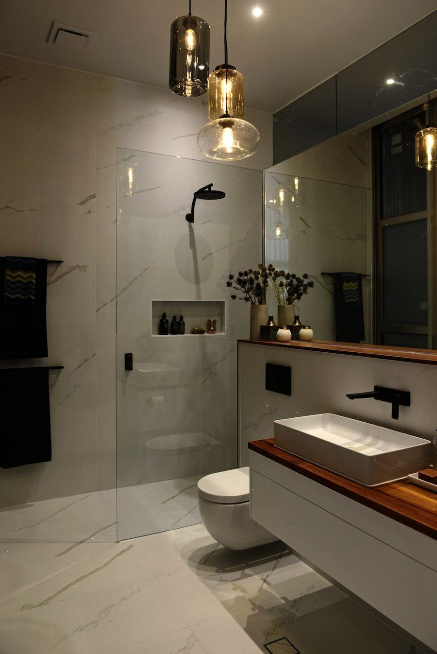 White marble wall tiles in bathroom \\/ wood shelf and wood bench in ...