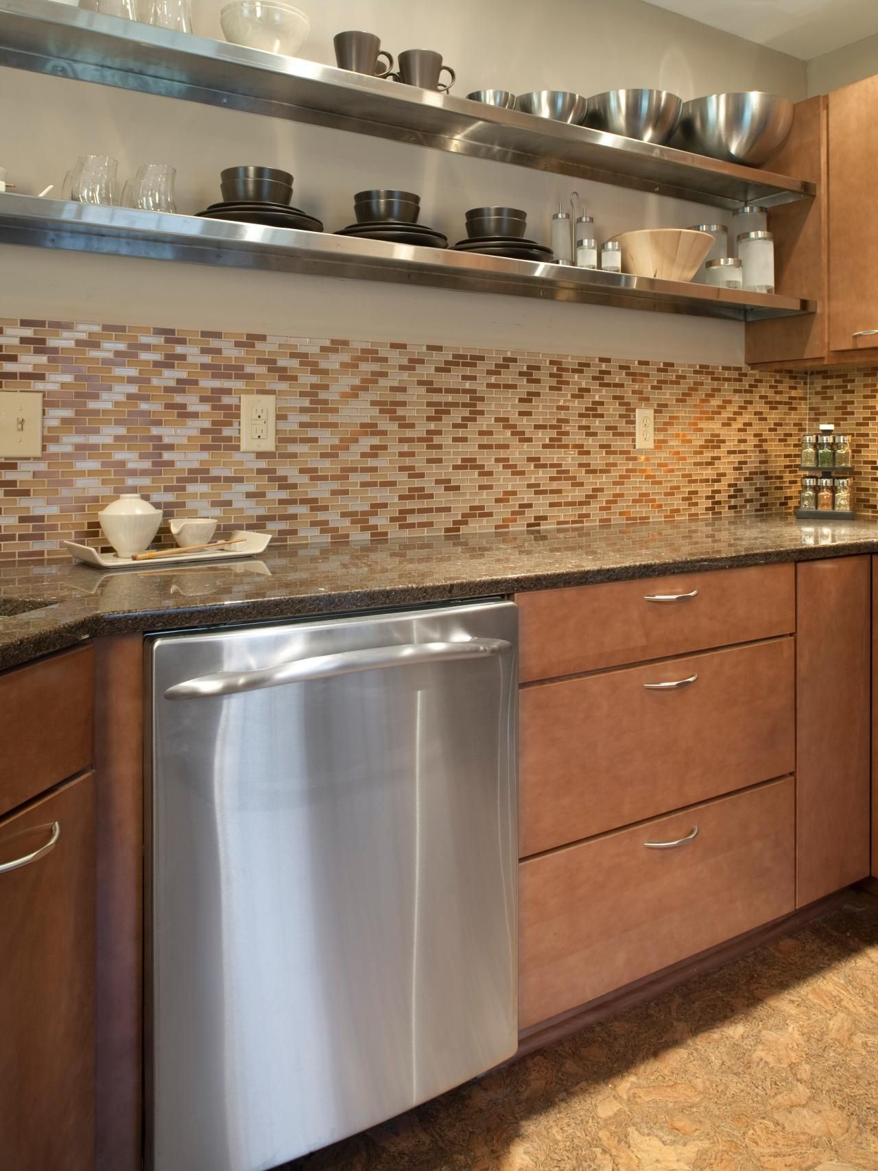 """Functionality meets contemporary design in this modern twist on the classic """"chef's kitchen."""" Stainless steel shelving works to conserve space while adding variation and depth to the neutral color scheme. A mosaic tile backsplash adds warmth and complexity to the space."""
