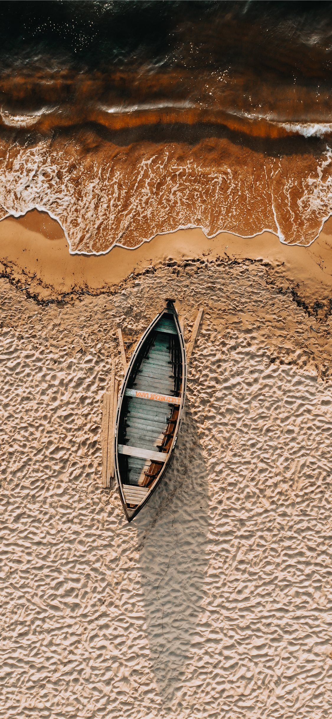 brown and white boat on brown sand iPhone 11 Wallpapers