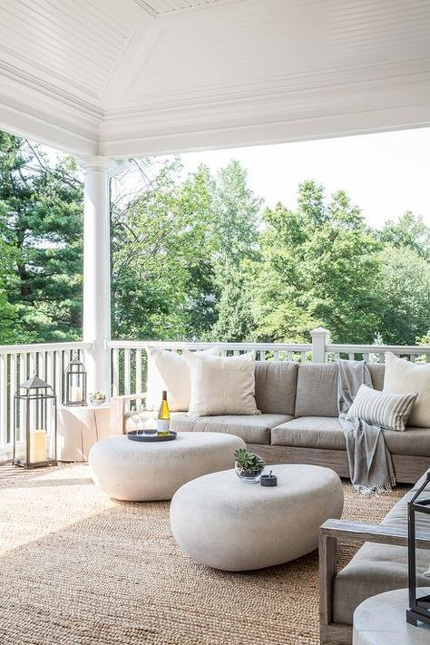 Modern Covered Patio Features A Low Armless Outdoor Sofa Lined With Ivory Pillows Facing Pair Of West Elm Pebble Coffee Tables Atop Jute Rug