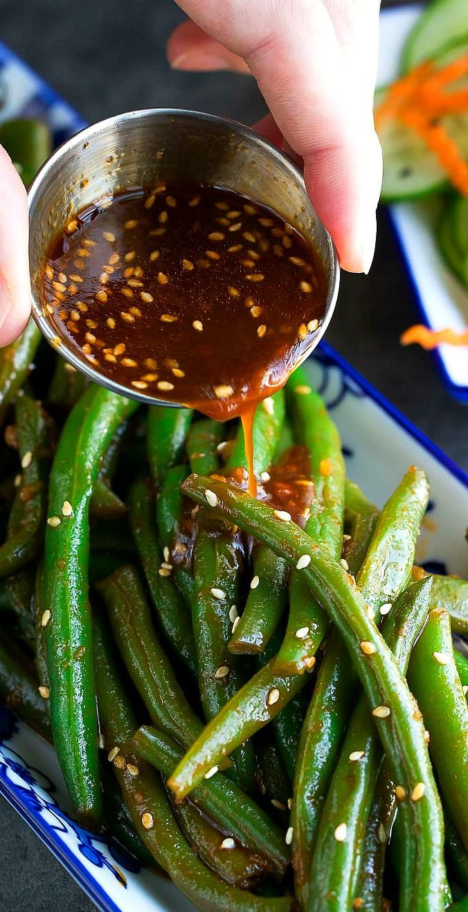 These Spicy Sriracha Green Beans are fast and flavorful veggie side dish! Grab some garlic and green beans and meet me in the kitchen for this fiery and delicious side dish! You'll only need 6 ingredients to whip up these spicy green beans in your kitchen. Green beans, garlic, sesame oil, Sriracha, sweet chili sauce, and soy sauce. You can also add toasted sesame seeds to the mix if you're feeling a bit extra.