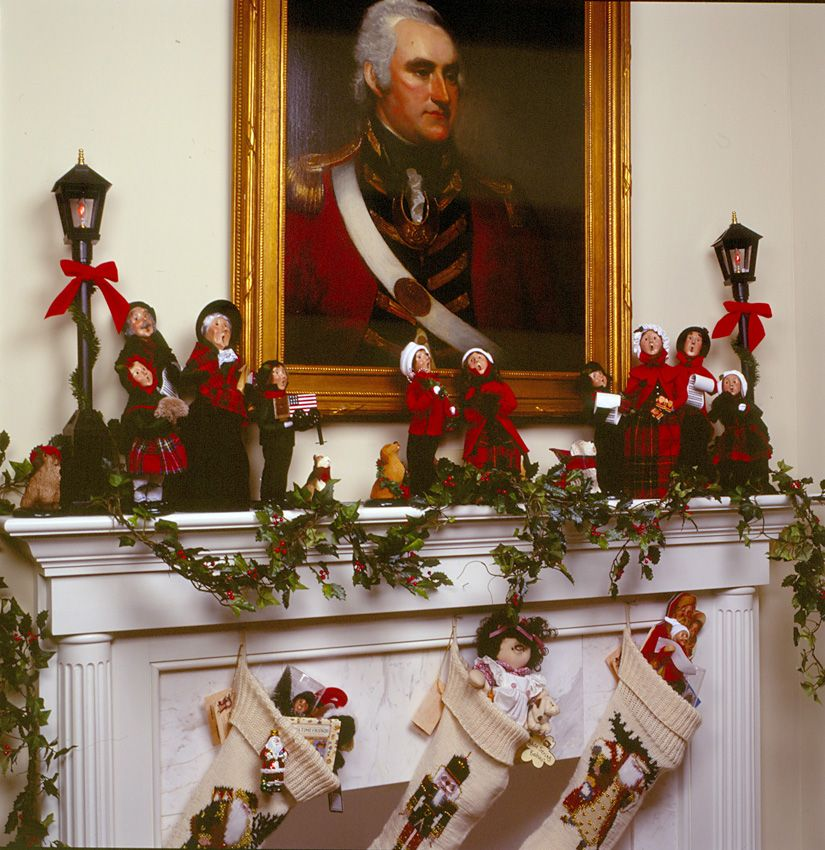 Carolers displayed on a mantle with garland and stockings