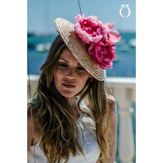 Gran tocado de paja natural o straw, ahormado sobre base de sinamay para adaptarlo al contorno de la cabeza de forma natural, con flores de tela artesanales.