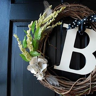 Use-what-you-have-wreath. Mix of handmade paper flowers, feathers, floral branches, twigs, monogram and patterned ribbon. [original source unknown]