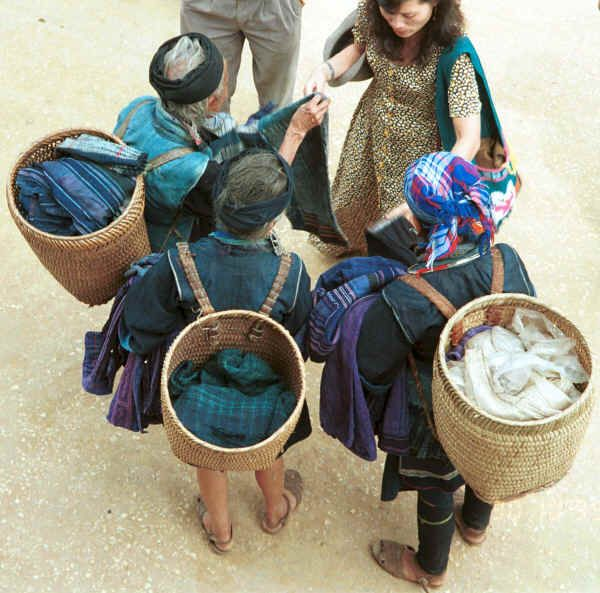 Jpeg 49K Black Hmong women trading old clothing with western tourists in the streets of Sa Pa, Lao Cai Province.  Some of the clothing has been over-dyed with turquoise or purple chemical dyes. 9510H34.JPG