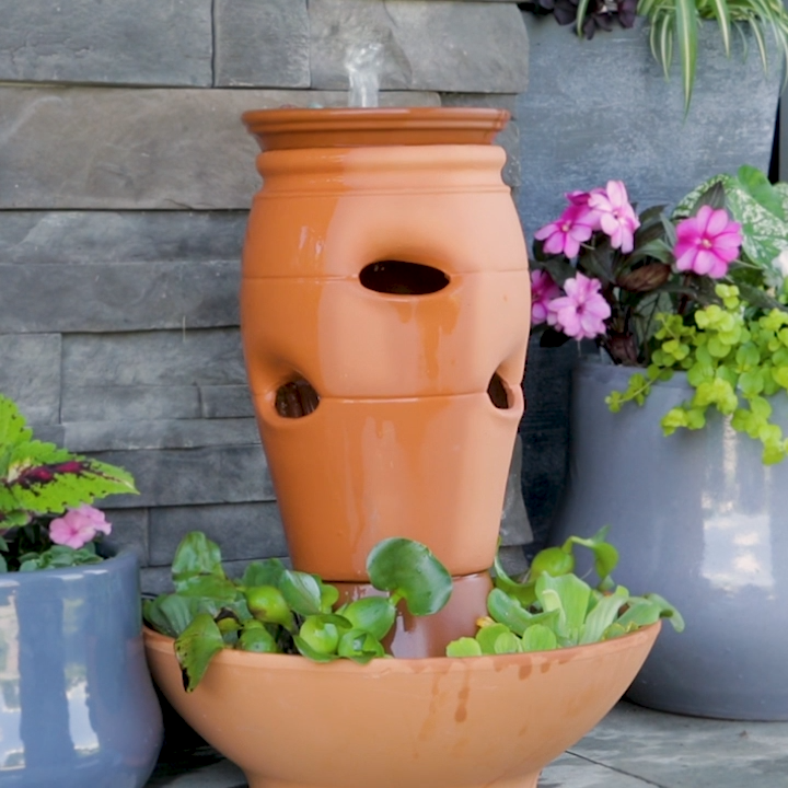 Terra-cotta strawberry planters are good for more than just planting herbs. Create this easy rustic garden fountain with just a few plumbing parts, a pump, and some terra-cotta pots. This is the perfect DIY for your backyard oasis. #outdoorfountain #backyarddiy #projectideas #bhg