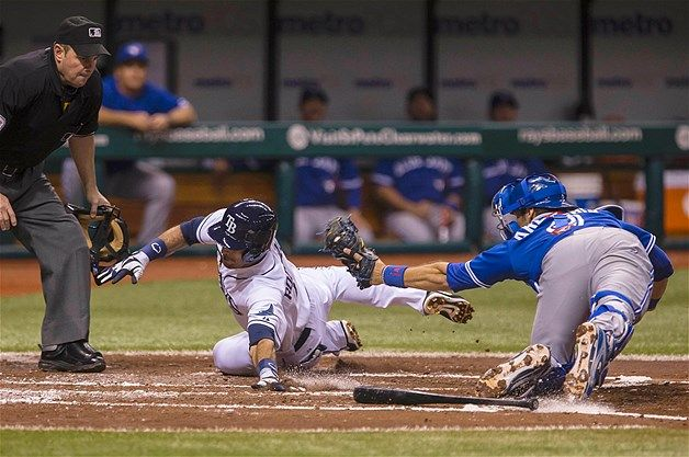 Tampa Bay Rays' Sean Rodriguez (center) slides into home plate past Toronto Blue Jays catcher J.P. Arencibia during the second inning of the...