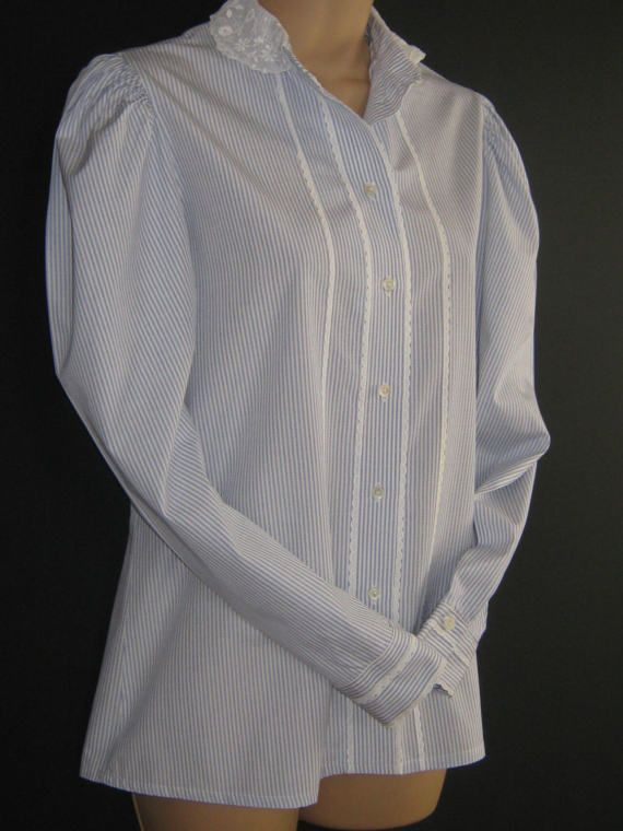 L A U R A A S H L E Y  I dont like ephemeral things, I like things that last forever  A RARE BLUE WHITE CANDY STRIPE COTTON BLOUSE IN EDWARDIAN/VICTORIAN STYLING. FRONT FASTENING WITH SEVEN MOTHER-OF-PEARL BUTTONS FROM THE DELICATE WHITE LACE TRIMMED, MANDARIN STYLE COLLAR DOWN TO HEM. DISTINCTIVE ROWS OF SCALLOPED BRODERIE ANGLAISE RUN PARALLEL TO THE BUTTON FRONT. THE GATHERED LEG O MUTTON SLEEVES TAPER INTO CLASSIC BUTTON CUFFS WHICH ARE ENHANCED WITH FURTHER BRODERIE ANGLAISE.  THIS ...