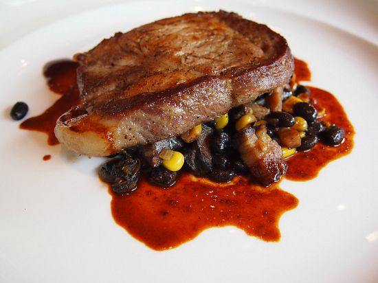 Kawartha Berkshire pork loin with a succotash of grilled corn, chipotle cured bacon, black beans, and coriander.