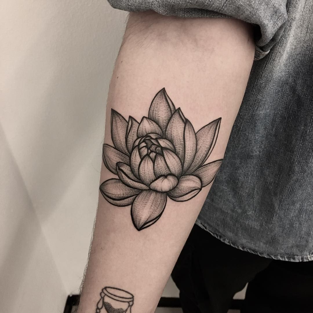 graphic lotus tattoo on forearm