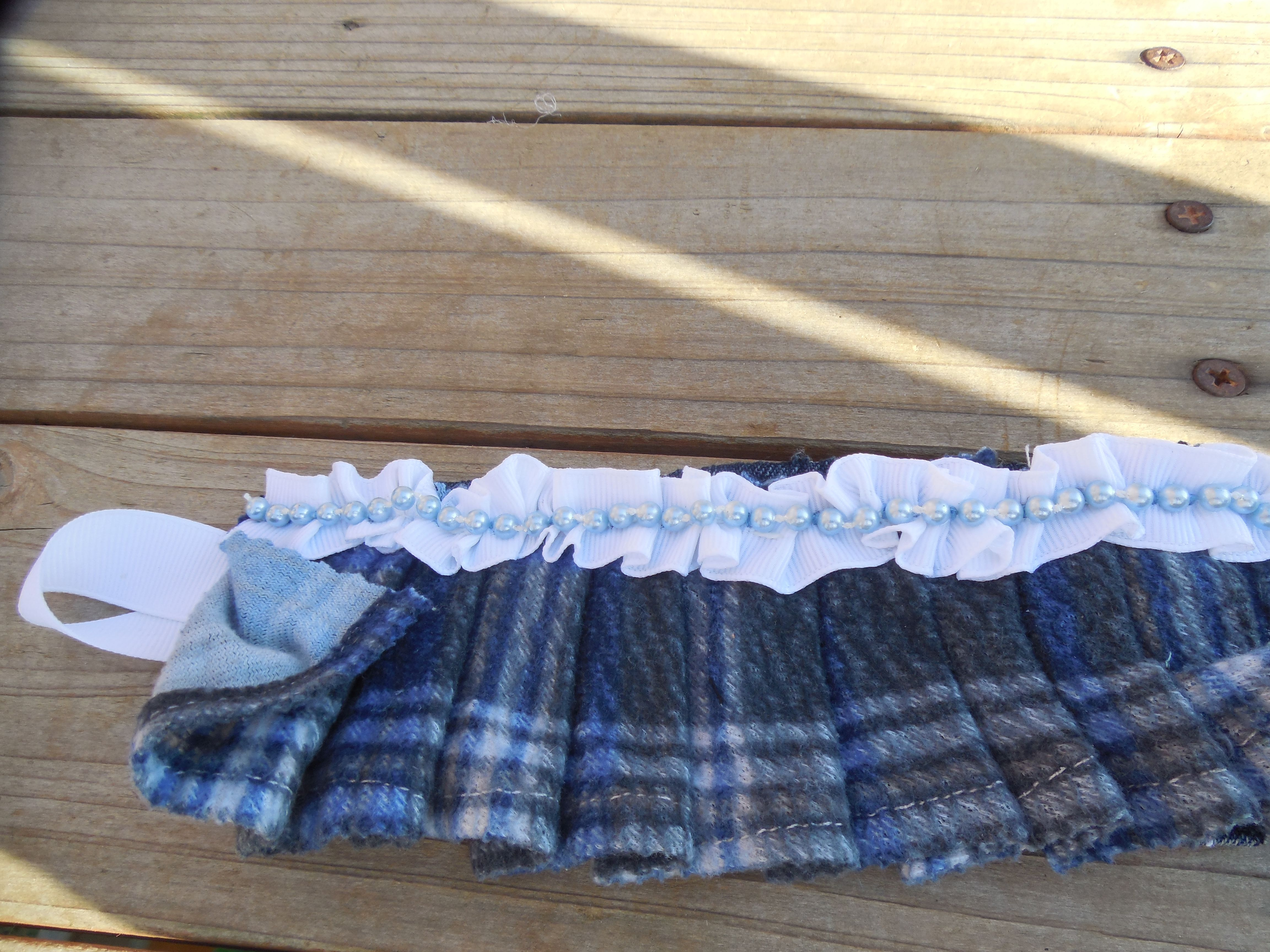 Denim base with a blue plaid ruffle and a white ruffled ribbon with blue pearls. Button loop to close.