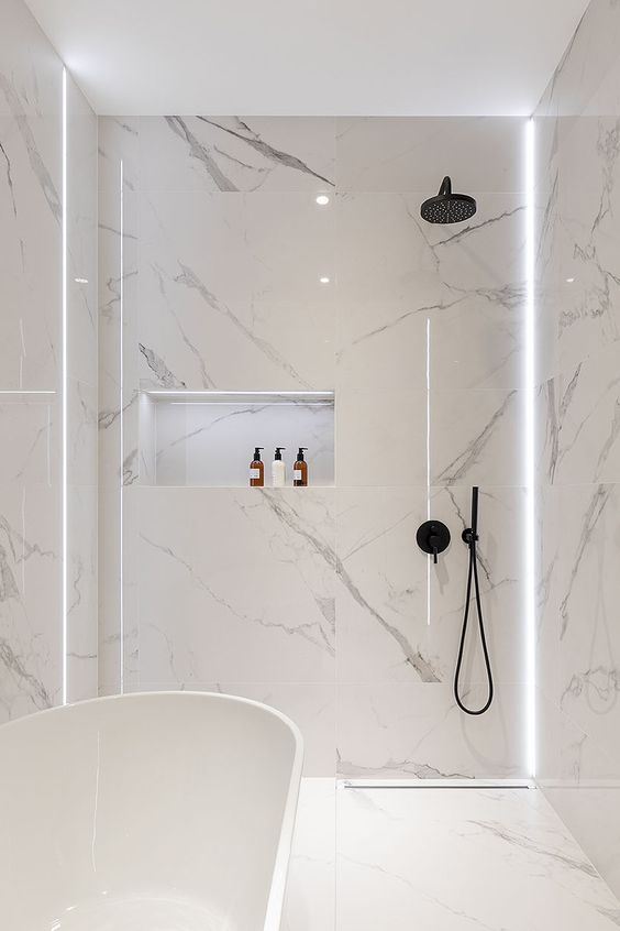 Photo of a minimalist white bathroom with white marble tiles, a free standing tub and mat…