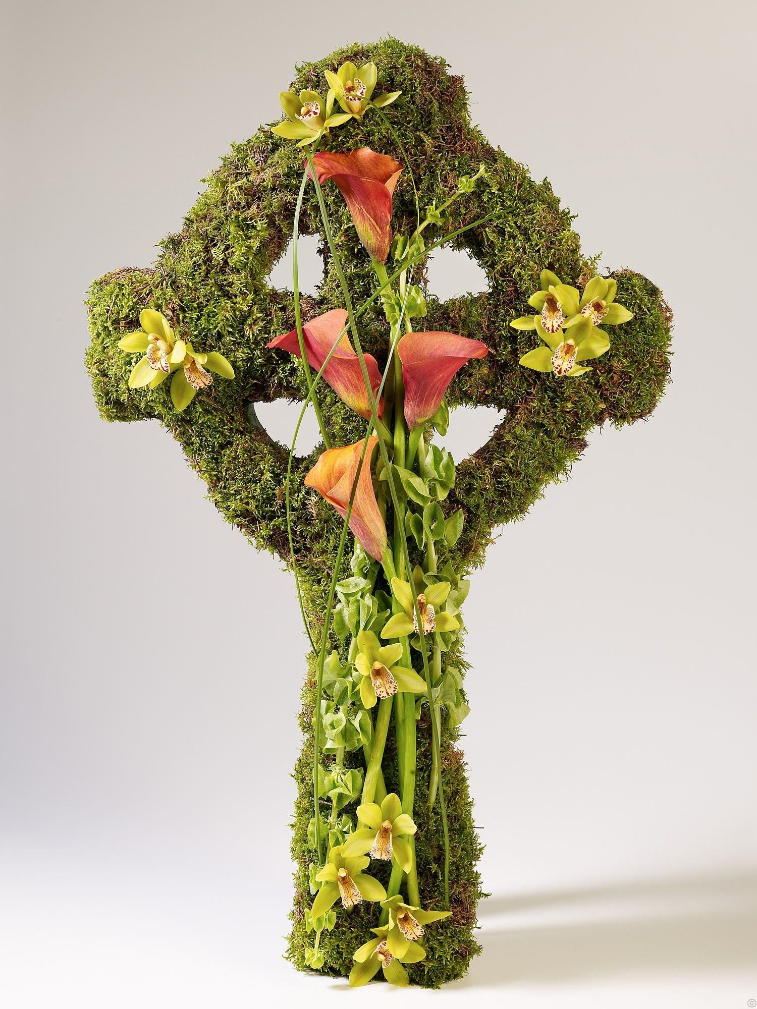Striking celtic cross moss croos with delicate green mini striking celtic cross moss croos with delicate green mini cymbidium orchids and elegant mango coloured calla lilies designed to be positioned flat izmirmasajfo
