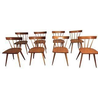 A stunning set of eight vintage Mid-Century designer Paul McCobb dining chairs, made of a warm honey colored wood. They have slat backs and all eight are in excellent vintage condition.