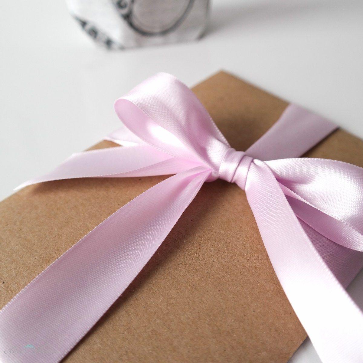 Kraftpapierumschlag zur Hochzeit mit rosa Schleife aus Satinband.