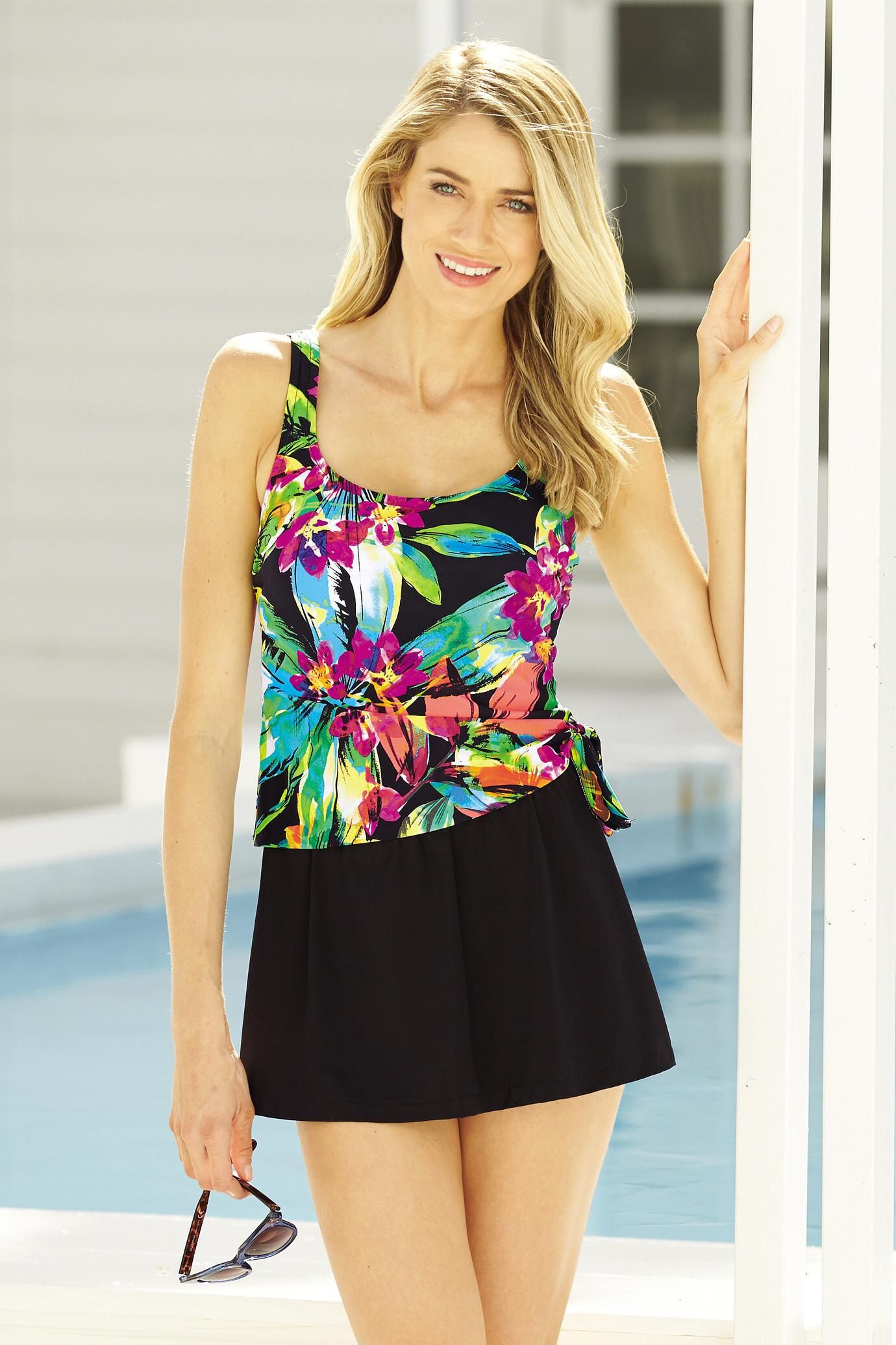 fe5649503ab01 Go tropical in this floral print swimsuit. This two piece bathing suit  gives you full coverage with a tankini top and skirted black bottoms.