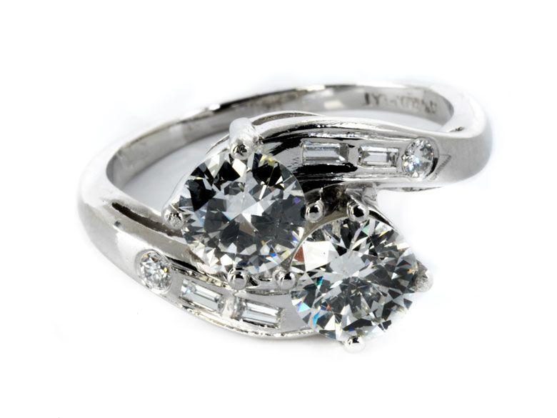 Ringweite: 55. Gewicht: ca. 5,8 g. Platin. Eleganter klassischer Zwillingsring mit zwei Altschliffdiamanten, je ca. 0,8 ct H/P1, flankiert von kleinen...