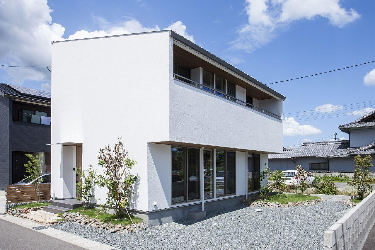 シンプルな箱型の家の周囲には石や芝 木と自然素材があることで族と