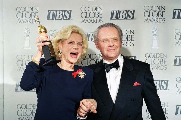 Actress Lauren Bacall holding up her Cecil B. DeMille Award for Lifetime Achievement as she holds hands with actor Anthony Hopkins backstage at the 50th annual Golden Globe Awards in 1993.