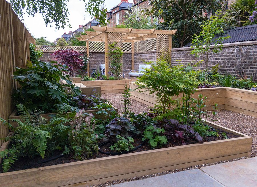 long walled garden with raised beds seating and an arbor on walled id=65530
