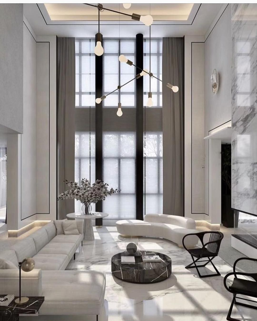 Double height all white. Love the marble fireplace wall ...