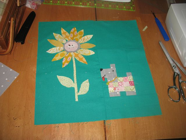 """the dog is pieced and the flower will be raw edge appliqued (although the stem is not raw-edged). nose, eye, mouth and collar are all embroidered.  using sherbet pips and a bunch of other prints in pink, green and yellow.  background is """"jade green"""" by moda bella solids."""