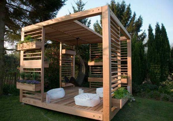 interessante gartnnlaube aus holz mit sitzkissen und hängesessel ... - Gartenpavillon Selber Bauen