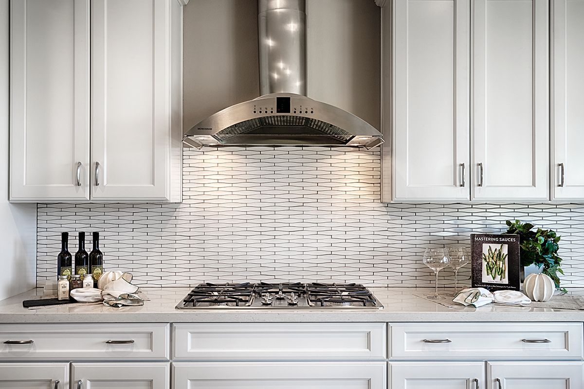 - Elongated Hexagonal Tile & A Curved, Stainless-steel Range Hood