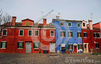 Photo made in the island of Burano in Venice in Italy. In the image they resumed colorful facades with very intense colors of some houses, narrow to each other, overlooking a square. Over the colors of the houses you see the pale blue color of the sky.