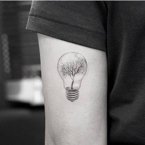 Surrealist tree light bulb tattoo on the back of the