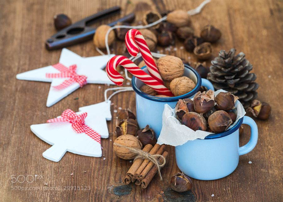 Pic: Traditional Christmas foods and decoration. Roasted chestnuts in blue enamel mug walnuts cinnamon