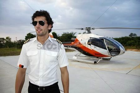 with sunglasses standing in front of helicopter stock photo Pilot with sunglasses standing in front of helicopter stock photo  Engineers writing on clipboard at construct...
