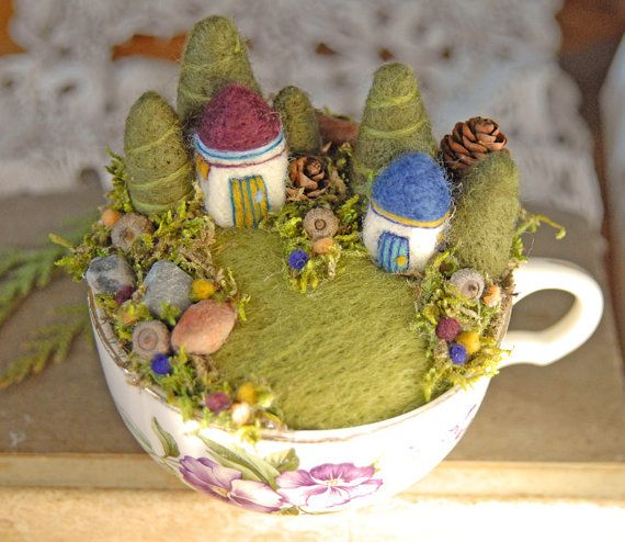 Carefully needle felted out of soft wool, these tiny houses, trees, and flowers nestle into a beautiful old teacup. The houses are surrounded by gardens made up of tiny acorns, pinecones, stones and moss. The cup has pretty purple flowers on the front which coordinate with the colorful houses and flowers. dsI am not sure who lives in these enchanting homes, but my guess is that it is fairies!    The cup ensemble is about 41/2 inches wide, counting the handle, by 3 1/2 inches tall. Since the…