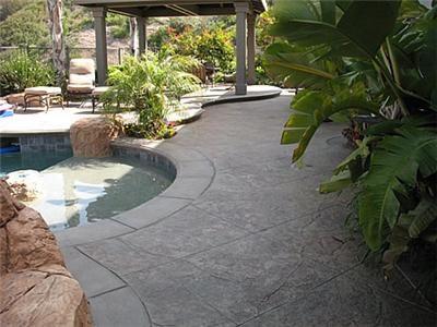 Stamped grey pool deck concrete pool decks artcon for Pool design hamilton