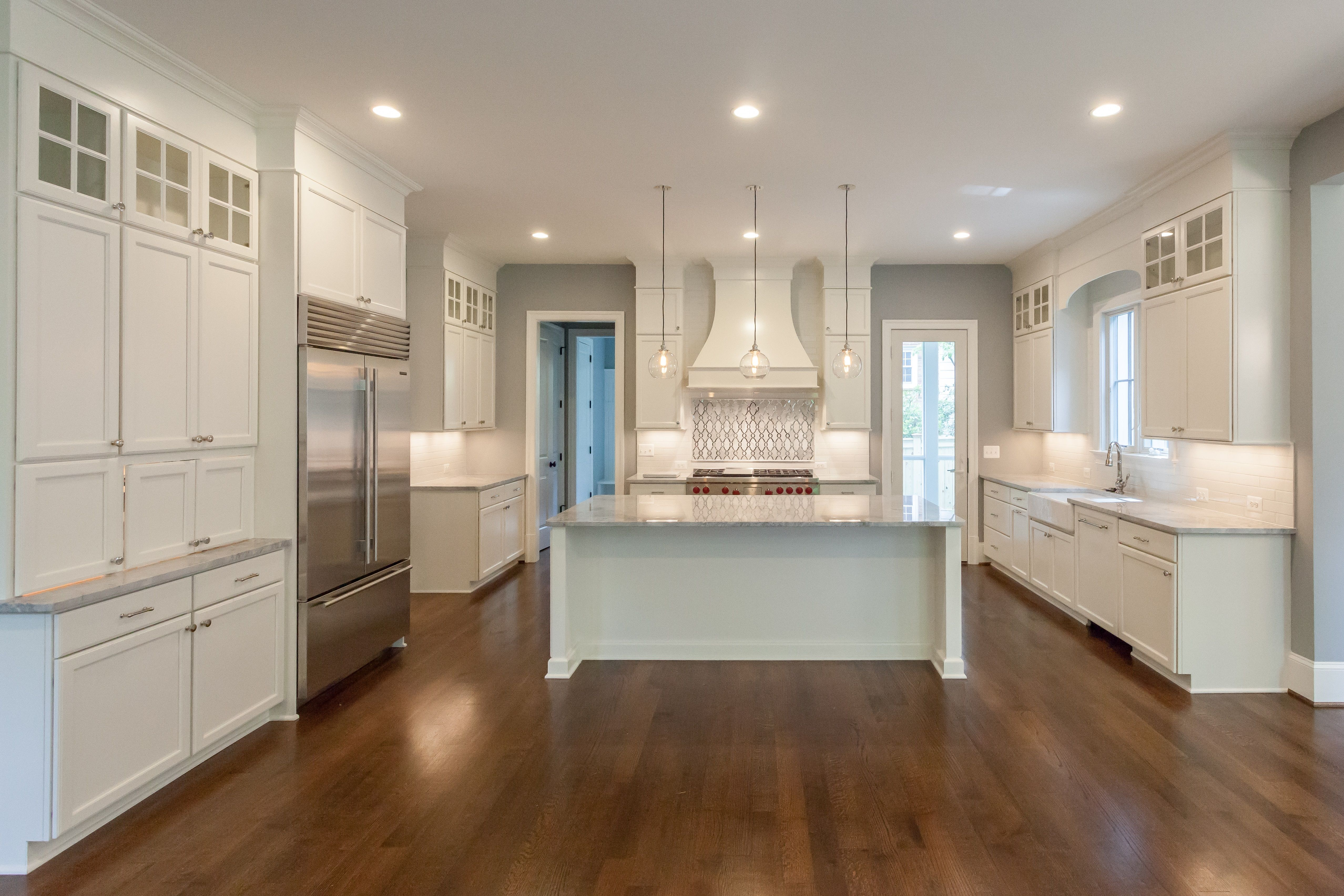 All White Transitional Kitchen With Feature Backsplash Over Range And Double Stacked Cabi Kitchen Cabinet Inspiration Kitchen Cabinets Kitchen Bathroom Remodel