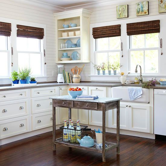 small, white kitchen with wood countertops and large wood knobs ...