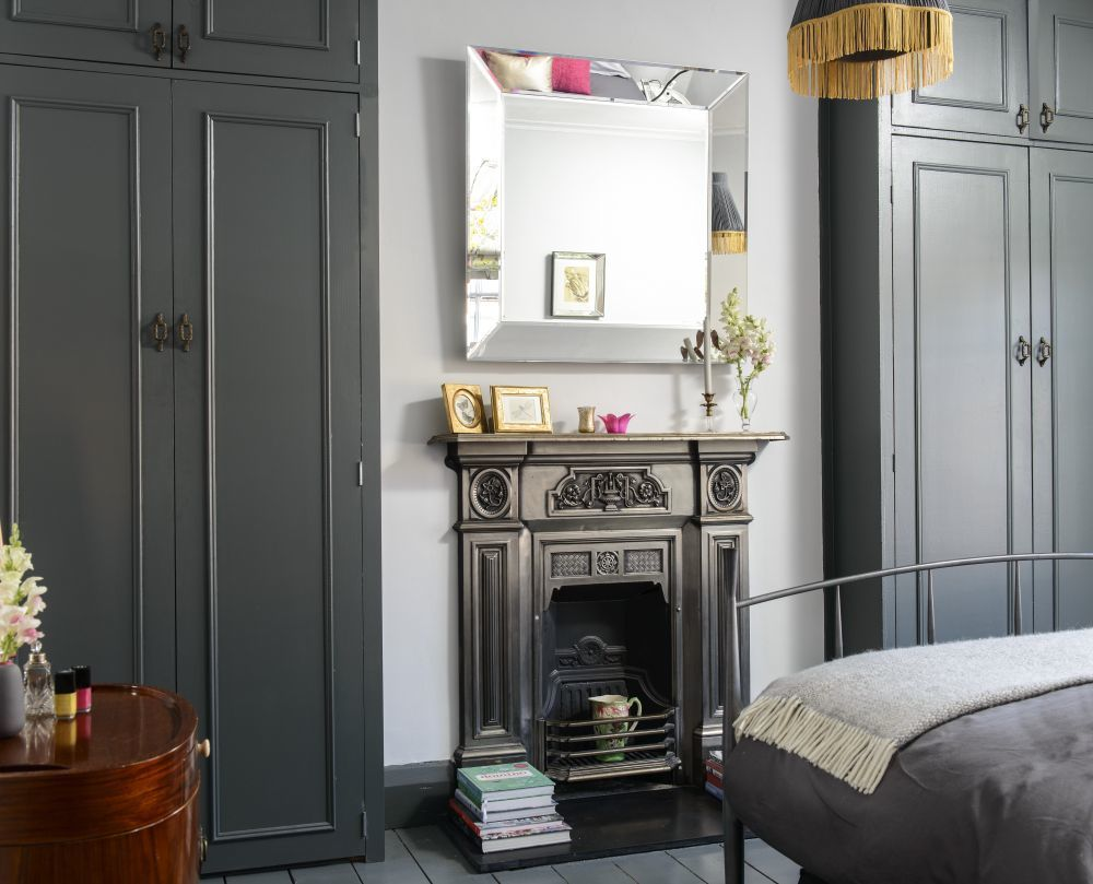 An understated mirror hangs above the fireplace ...