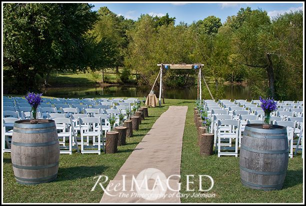 A beautiful outdoor ceremony with a burlap aisle runner, rustic cedar log arbor, and oak whiskey barrels.