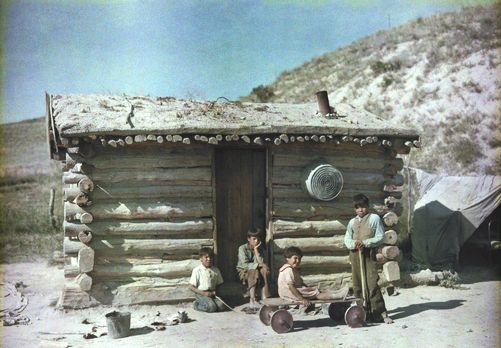South Dakota - Boys pose outside a sod roof house at the Pine Ridge Reservation