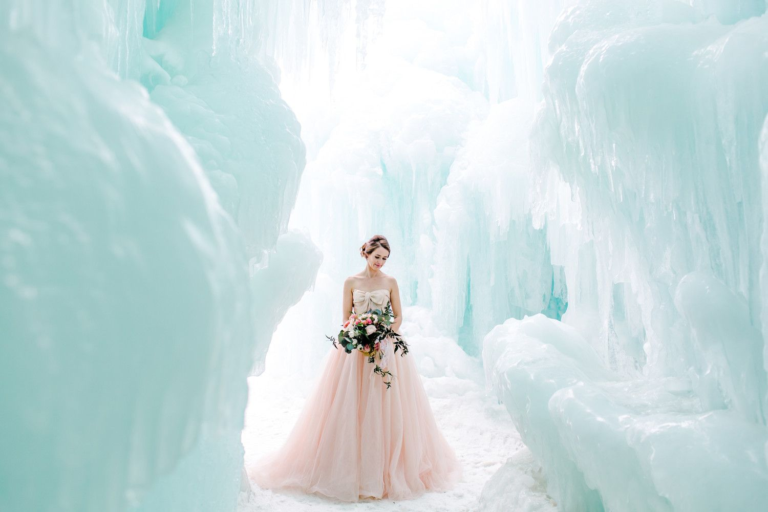 Here, a peachy-pink wedding dress pops against a barely-blue ice ...