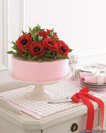 Bright sugar poppies are planted atop a cake iced in blush-colored buttercream.