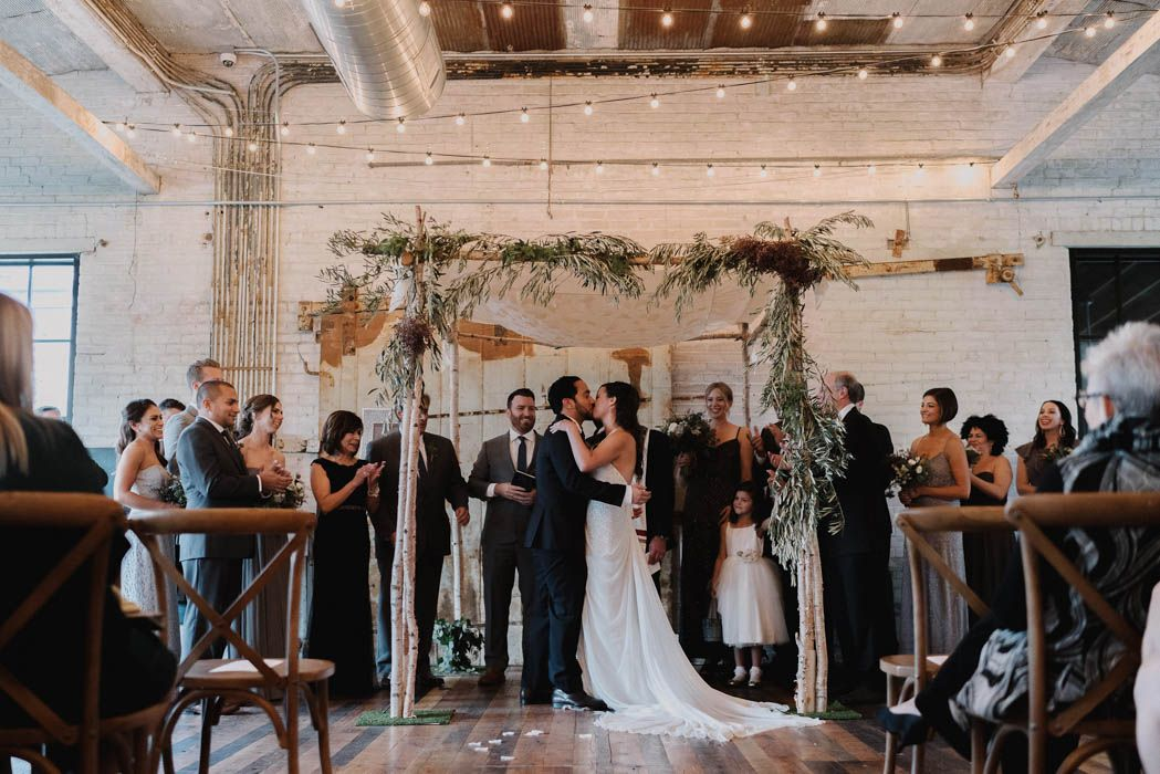 Sweet first kiss as newlyweds under the chuppah at this distillery wedding in Michigan | Image by  Sally O'Donnell Photography