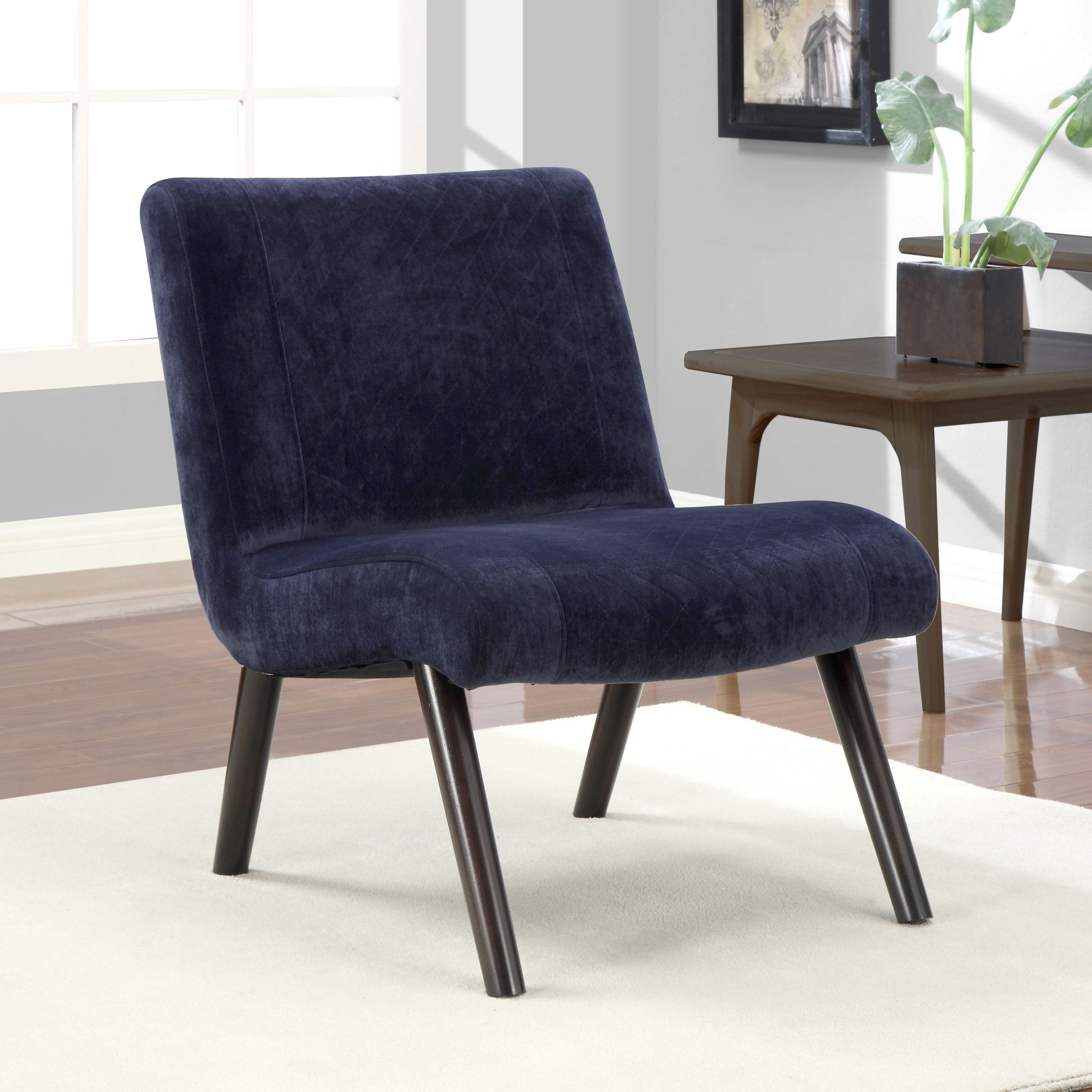 The simple, clean lines of this modern style chair are enhanced by a beautiful quilted section down the center of the chair. This armless chair exhibits a soft velvet like fabric, which makes it a must have for every home.
