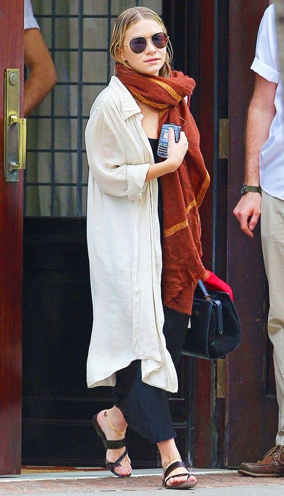 Ashley Olsen wears a black top, loose sandals, a long white shirt, slide sandals, aviator sunglasses, a thick orange scarf, and a black satchel bag