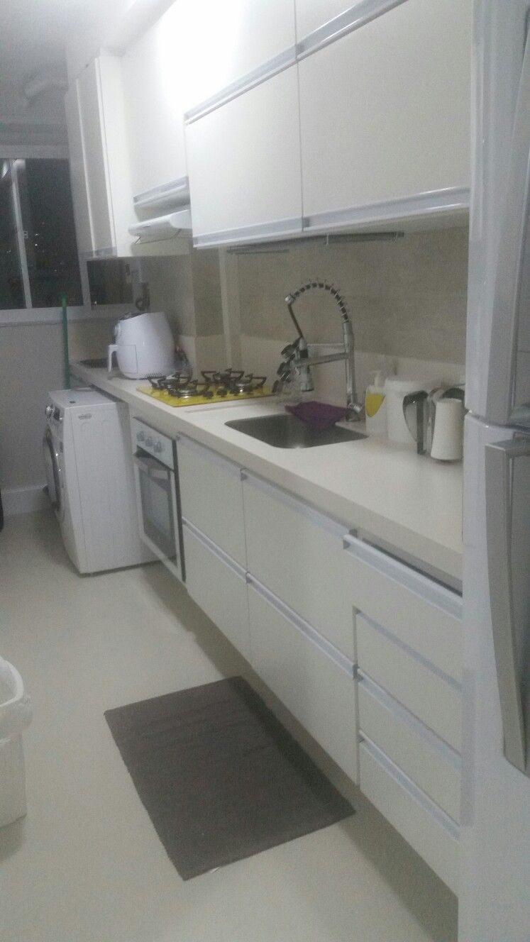 O amarelo do cook top no armário desenvolvido pela marcenaria para aproveitar todos espaços e tapar os encanamentos aparentes dos imóveis de alvenaria estrutural