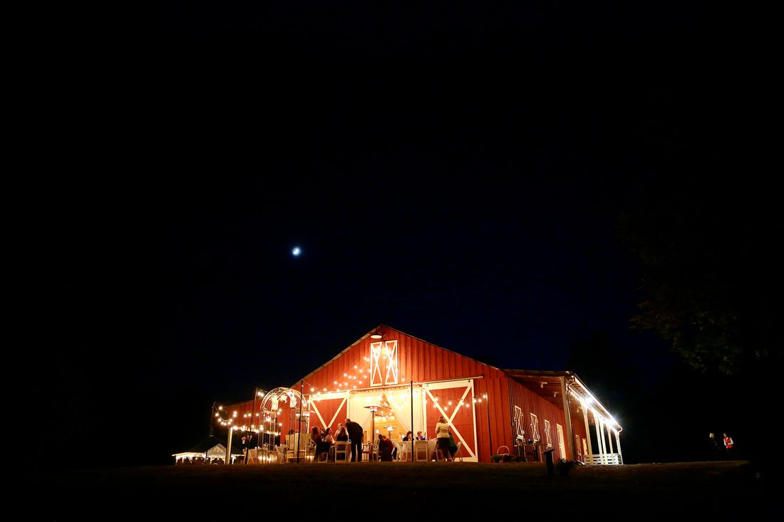Red Barn Wedding Lit Up At Night With Cafe Lights Hung From The Hay