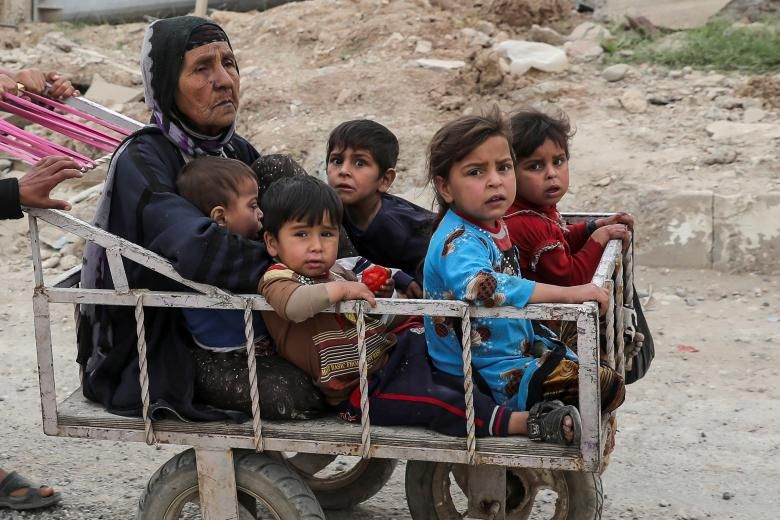A displaced Iraqi woman and children are transported in a cart as the battle between the Iraqi Counter Terrorism Service and Islamic State militants continues nearby, in western Mosul, Iraq. REUTERS/Marko Djurica