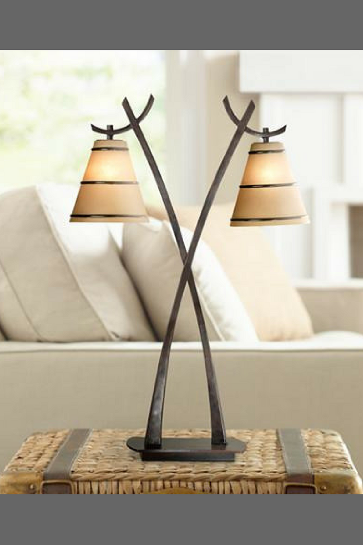 This striking table lamp features two bulbs housed in amber glass this striking table lamp features two bulbs housed in amber glass shades for an inviting ambient glow its asian inspired crossed sickle like arms are aloadofball Choice Image