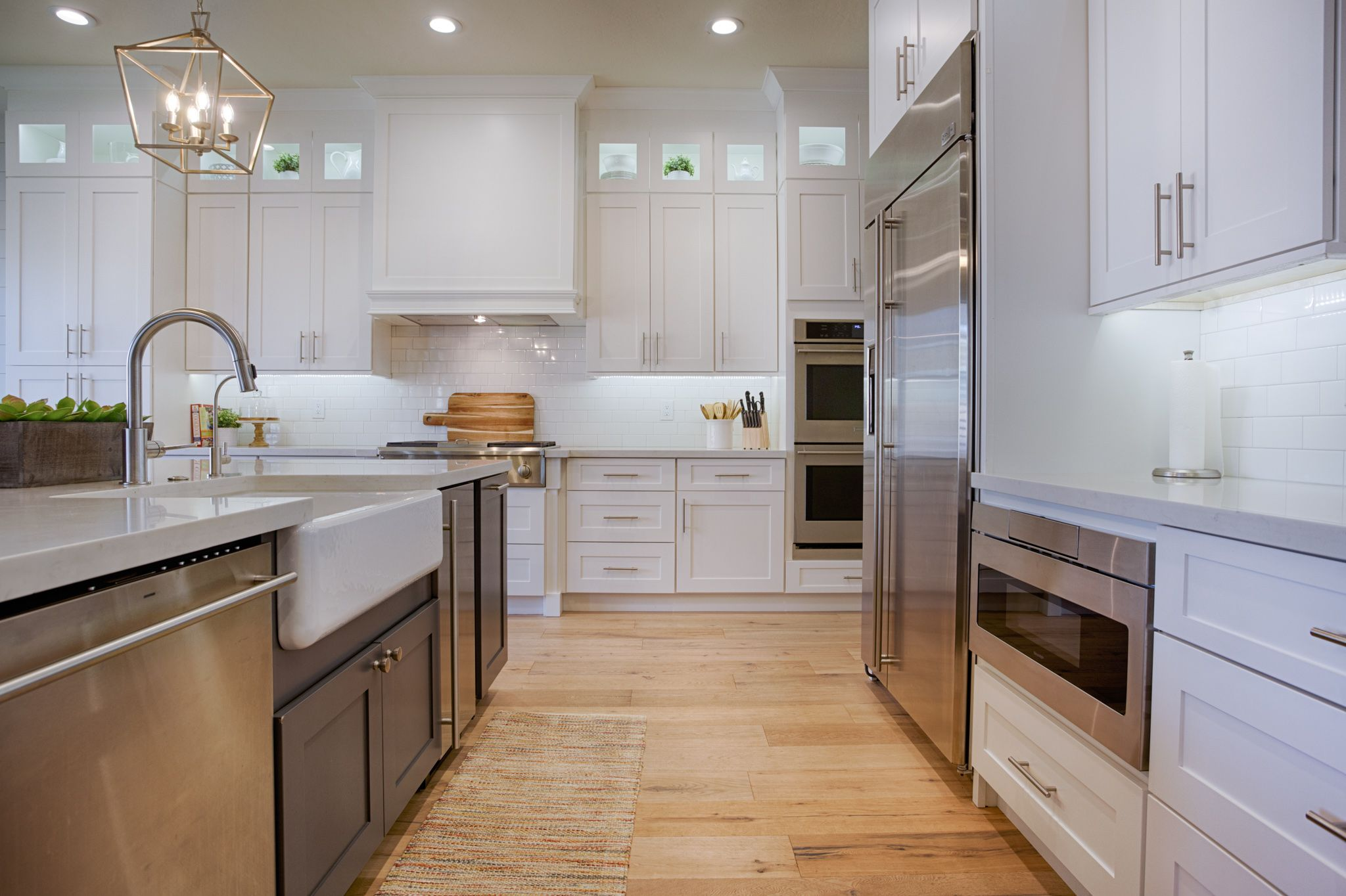 White Shaker Cabinets Gray Island And Light Wood Floorings Create Such A Soft Inviting Atmosphere In The Kitchen Custom Kitchen Cabinets Kitchen New Kitchen